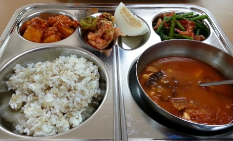 Yesterday's school lunch consisted of spicy kimchi soup with pork, rice, green beans with dried shrimp, kimchi, tofu dressed in a vegetable tomato sauce and a slice of a Korean melon.
