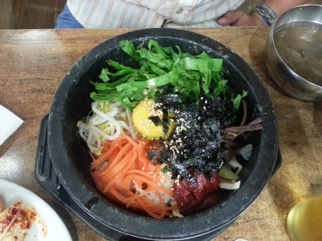 Dolsot bibimbap is served in a sizzling hot stone pot. The raw egg starts to cook when you mix everything together.
