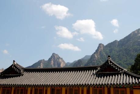 Korean rooftops and craggy peaks.