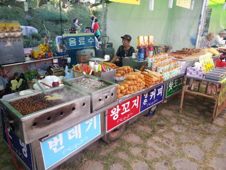 A typical snack booth seen at Korean festivals, which includes bubbling silk worms, corn dogs, fried chicken and a variety or skewered meat.