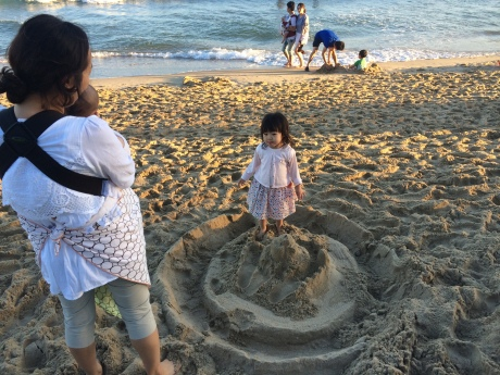 This little girl really wanted to destroy our sand castle. It was adorable.