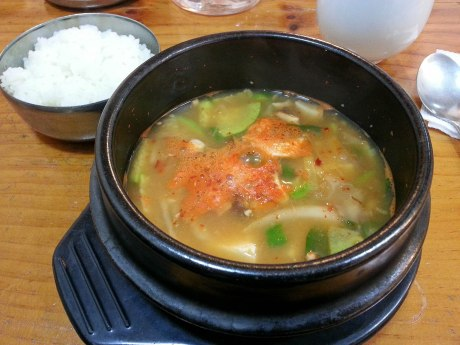 Doenjang jjigae is served sizzling hot in a stone bowl along with a side of rice.