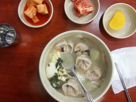 A steaming bowl of tteok mandu guk, which could easily become just mandu guk by removing the rice cakes.  As usual, kimchi, radish kimchi and pickled daikon radish are served as sides.