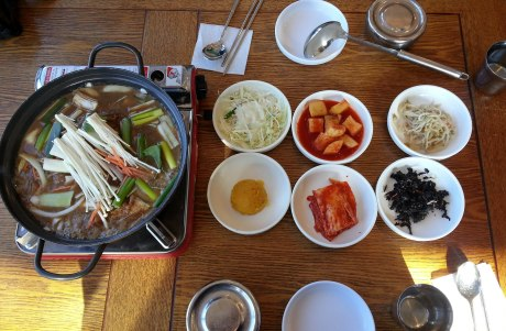 Bulgogi that is being pan-cooked at our table with traditional side dishes of cabbage salad, cubed radish kimchi, bean sprouts, mashed sweet potato, kimchi and dried seaweed. It was all delicious!